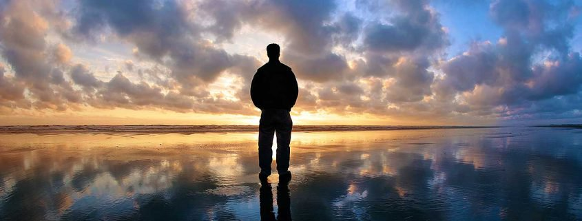 man standing on shore at sundown
